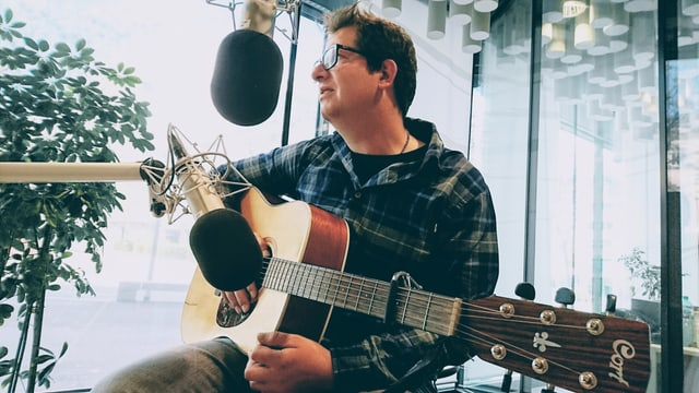 Curdin Nicolay cun sia ghitarra en il studio da radio.