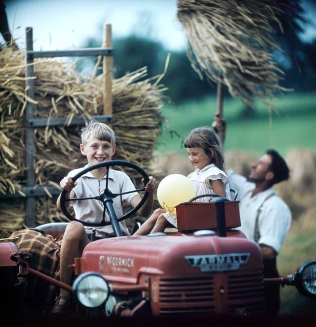 Ein Junge sitzt fährt lachend einen Traktor, neben ihm sitzend ein lachendes Mädchen, dahinter ein Mann, der Getreide mit einer Heugabel auf den Traktor schichtet.