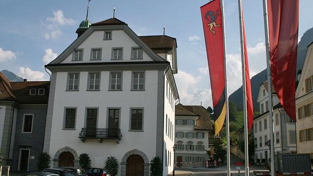Ein weisses Haus, vorne stehen Flaggen.