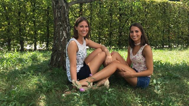 Franziska und Julia sitzen auf einer Wiese.