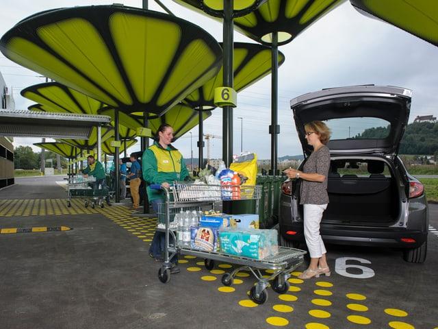 Migros-Angestellte bringt Produkte zum Auto einer Kundin