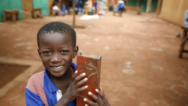 Symbolbild: Schwarzer Junge auf einem Dorfplatz.