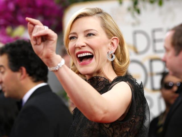 Schauspielerin Cate Blanchett lacht und gestikuliert auf dem Roten Teppich.
