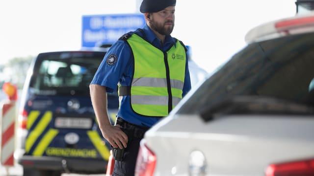 Beamter der Grenzwache kontrolliert ein Fahrzeug