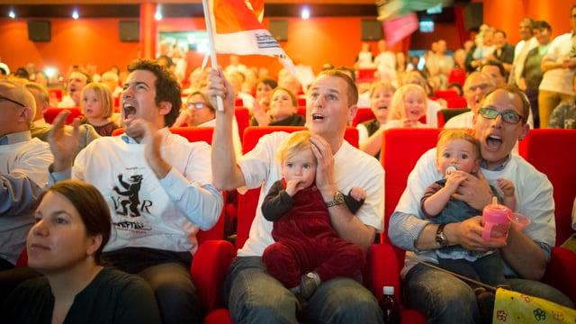 Menschen jubeln im Kinossal und feuern an.