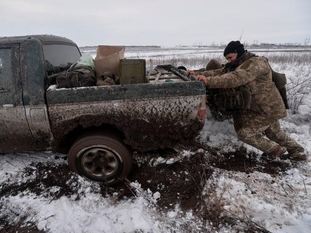 Soldaten schieben Truck an, der im Matsch feststeckt