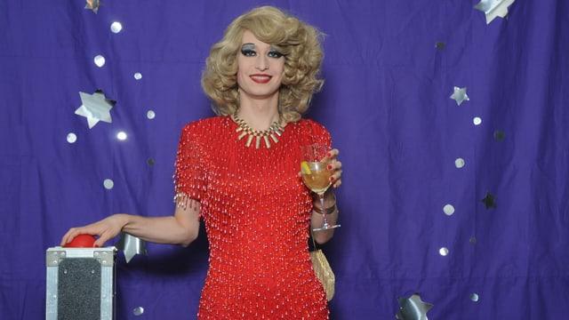 eine Drag Queen in rotem Kleid vor blauem Hintergrund