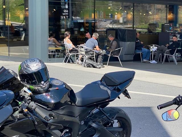 Motociclists che sesan sin ina terrass sper lur motos.