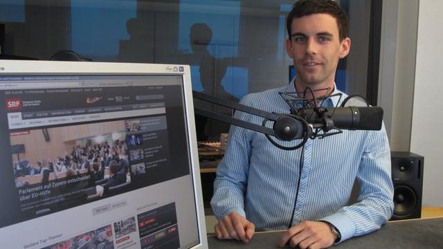 Ein Mann in blauweissem Hemd vor Mikrofon.