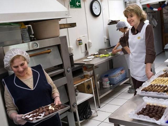 Zwei Frauen in Arbeitskleidung in einer Schokoladenfabrik
