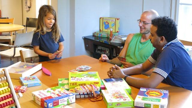 Zwei Männer und ein Kind spielen Uno.