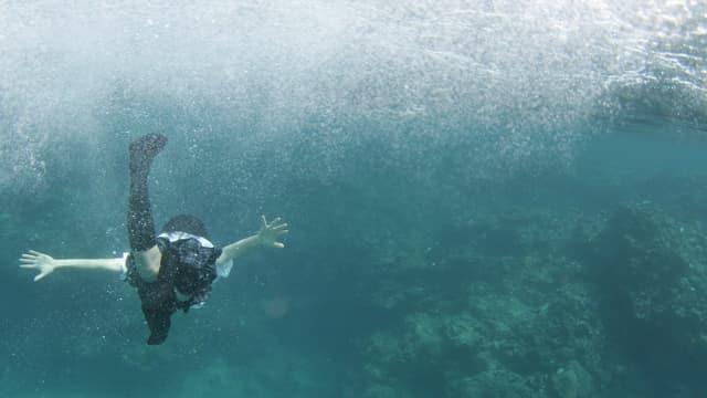 Ein Mädchen schwimmt bekleidet im Meer.