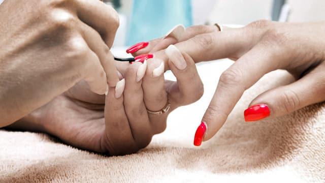 Eine Frau lackiert einer anderen Frau die Fingernägel rot.