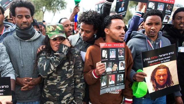 Schwarze Männer und eine Frau halten Plakate in die Höhe.