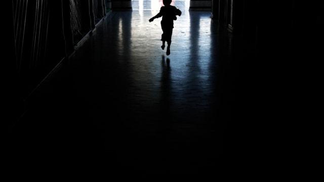 Kleiner Junge rennt in dunklem Gang