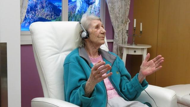Ältere Frau sitzt in Sessel und trägt Kopfhöhrer