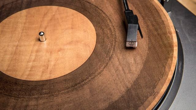 Ein Schallplattenkopf auf einer hölzernen Schallplatte.