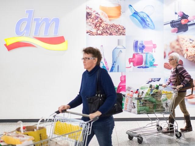 Zwei Frauen stossen ihre vollgepackten Einkaufswagen aus der DM-Filiale im Einkaufszentrum Lago in Konstanz. (keystone)