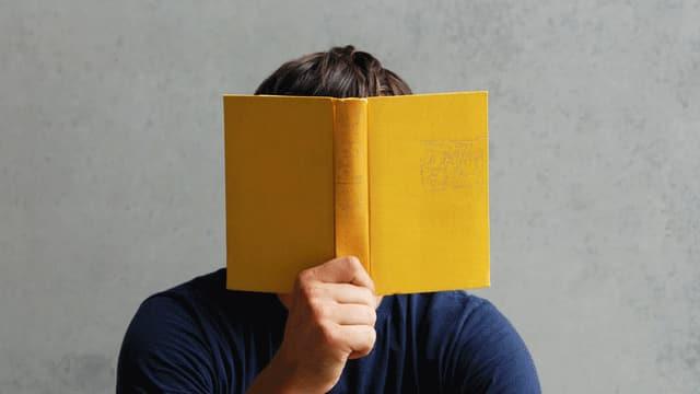 Ein Mann hält sich ein gelbes Buch vor den Kopf.