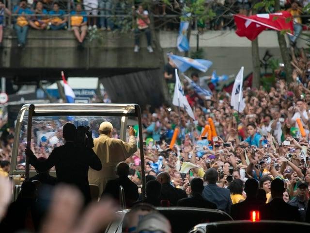 Das Papamobil von hinten gesehen, umringt von den Massen, die den Pontifex feiern.