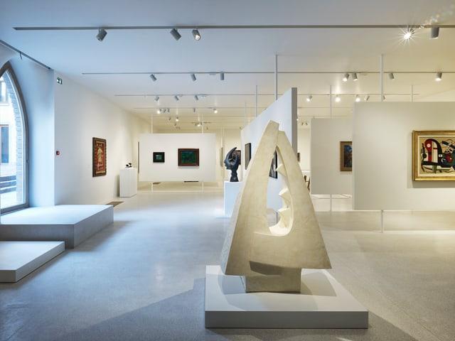 Eine Skulptur und Bilder in einem Ausstellungsraum.