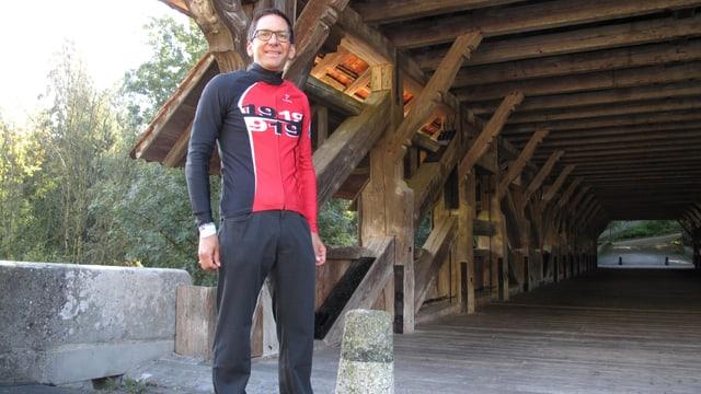 Ein Mann steht im Velotricot vor einer Holzbrücke.