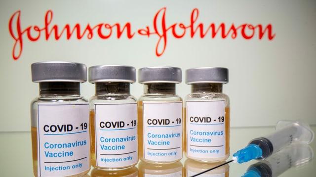 Vier Dosen des Impfstoff Johnson & Johnson mit einer Spritze und im Hintergrund das Logo von J&J