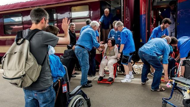 Voluntars che gidan a persunas en sutgas da rodas en il tren.