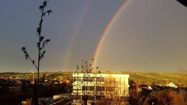 Ein doppelter Regenbogen über einem Haus.