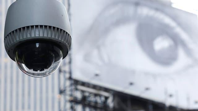 Eine Überwachungskamera, dahinter ein Plakat mit der Grossaufnahme eines Auges.