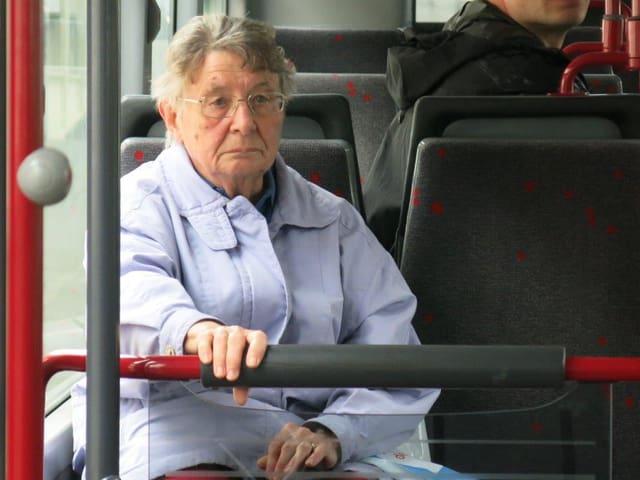Eine ältere Frau sitz im Bus und hält sich an einer Stange fest.