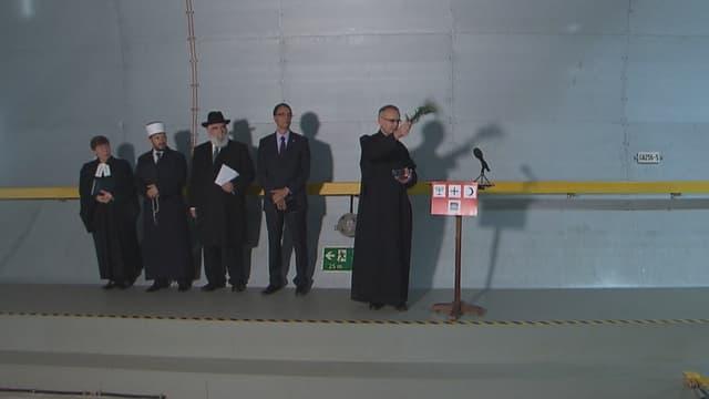 Tschintg sacerdots da las grondas religiuns e confessiuns en svizra benedeschan il tunnel dal Gottard. Els stattan en ritscha davon ina paraid.