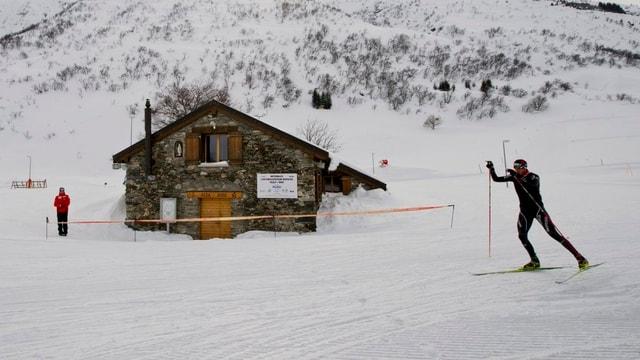 Biathlontraining im Schnee mit einer Hütte im Hintergrund.