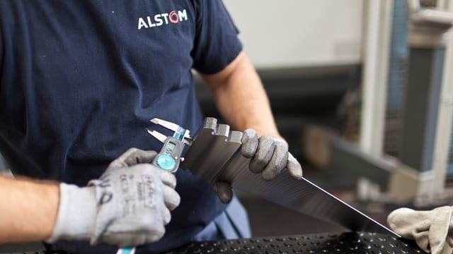 Ein Mitarbeiter bei der Arbeit mit einem Metallstück.