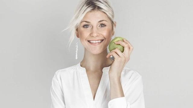 Eine blonde Frau hält sich einen grünen Apfel an die rechte Wange.