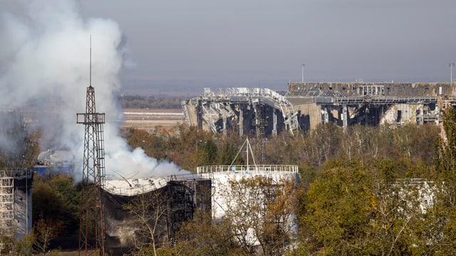Rauch seigt auf aus den Trümmern der zerschossenen Abflughalle des Donezker Flughafens.