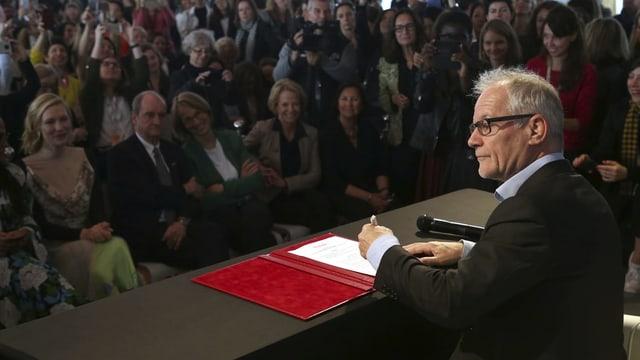 ein Mann unterschreibt an einer Pressekonferenz vor Journalisten ein Dokument.