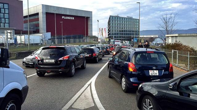 Stehende Autos auf einer Autobahnkreuzung. Im Hintergrund die Gebäude des Gewerbeviertels von Pratteln.
