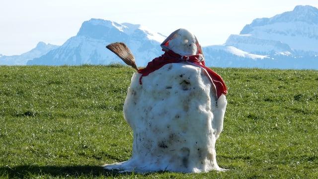 Tauwetter: Reste eines Schneemannes auf grünen Wiese. Im Hintergrund Schnee in den Alpen.