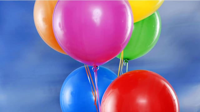 Luftballons in bunten Farben vor blauem Himmel.