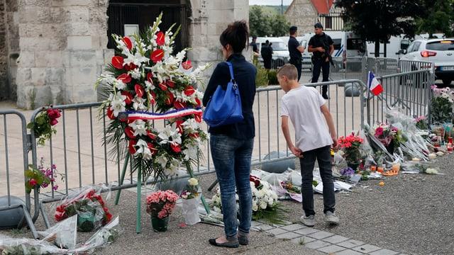 Frau und Junge schauen Blumenkränze vor der Kirche in Saint-Etienne-du-Rouvray an