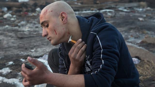 Ein Flüchtling mit kahlrasiertem Kopf rasiert sich draussen, mit einer Glasscherbe als Spiegel. Er hat sich an mehreren Stellen geschnitten und blutet.