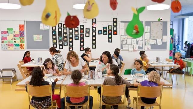 Kinder sitzen in einem Hort zum gemeinsamen Essen am Tisch