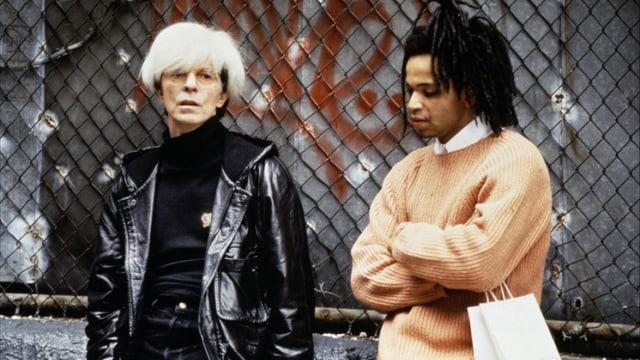 Andy Warhol und Basquiat stehen vor einem Maschendrahtzaun.