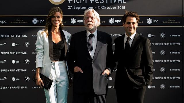 Nadja Schildknecht, Donald Sutherland und Karl Spoerri vor Fotowand posierend.