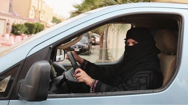 Eine verhüllte saudische Frau sitz am Steuer eines Autos.