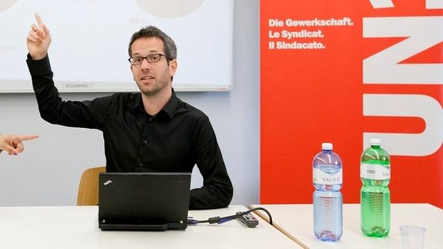 Roman Burger bei einer Medienkonferenz mit erhobener rechter Hand.