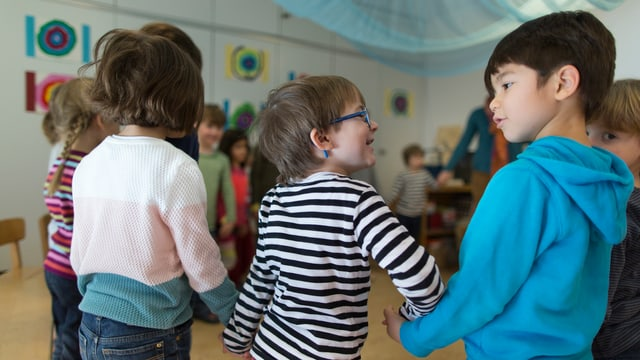 Kinder im Kindergarten lächeln sich an.