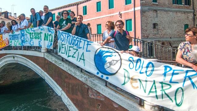 Eine Brücke über einen Kanal ist mit Protesttransparenten behangen. Auf der Brücke stehen die Protestierenden.