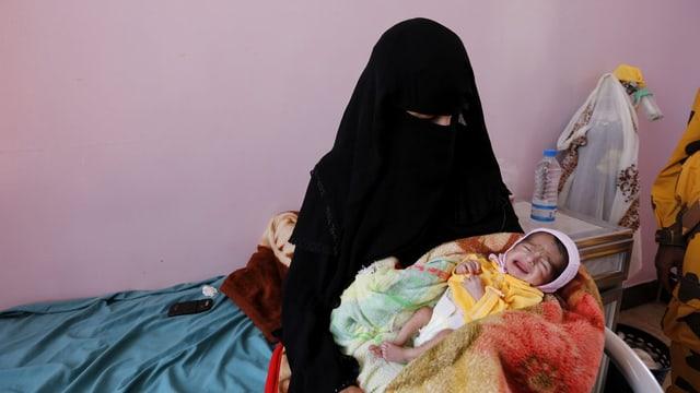 Frau in Burka mit Säugling mit rosa Käppchen